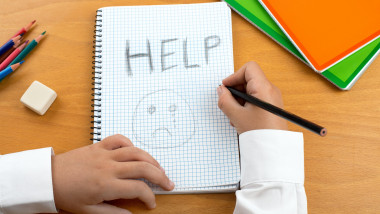 An image /poster covering the Social Issues of child abuse, schoolchild in uniform at a desk asking for help by a written