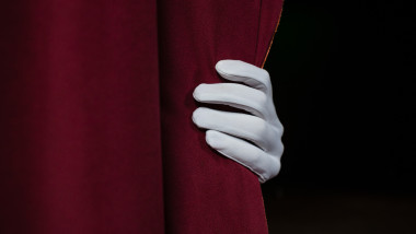 Hand in a white glove pulling curtain away