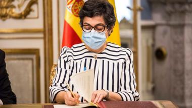 Ministrul de externe al Spaniei, Arancha Gonzalez Laya, cu ochelari si masca, semneaza intr-o carte de oaspet
