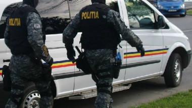 politisti cu uniforme de protectie langa o masina de politie