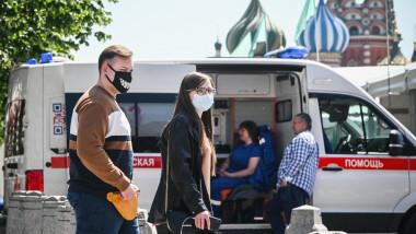 Trecători în Moscova, lângă o ambulanță.
