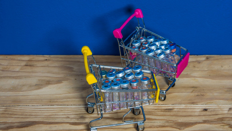 A small shopping basket filled with coronavirus vaccines against the background
