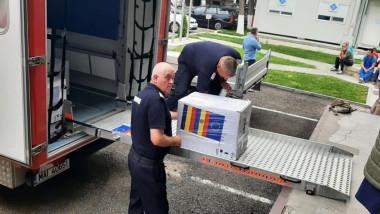 Doi angajați ai ISU descarcă mai multe cutii cu vaccinuri dintr-o mașină.