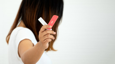 Teenager holding two pregnancy test cassettes with positive result on white background with copy space