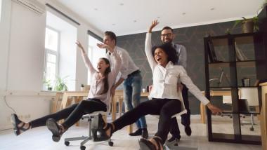 barbati imping cu scaunele doua femei angajati fericiti la birou