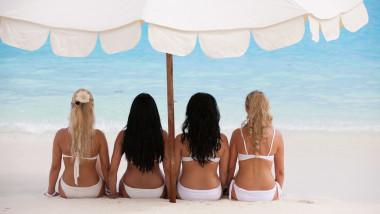 Patru femei stau pe plajă sub o umbrelă.