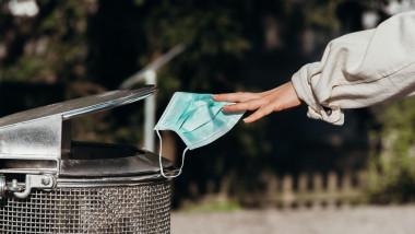 Un om aruncă o mască de protecție într-un coș de gunoi