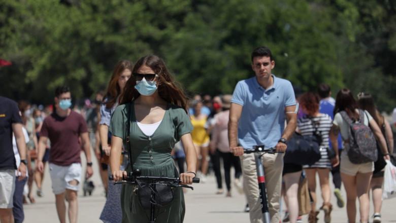 Trecători în parc cu mască de protecție sau fără