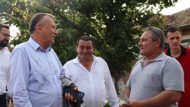 Nicolae Dobre (stânga), in camasa transpirat cu haina pe brat si telefon in mana sta de vorba cu un localnic si zambeste