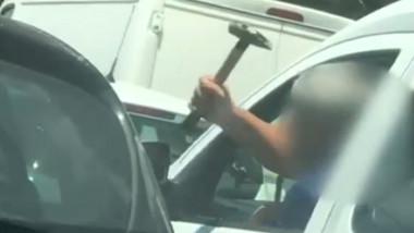 Șofer cu un ciocan în mână, în trafic.