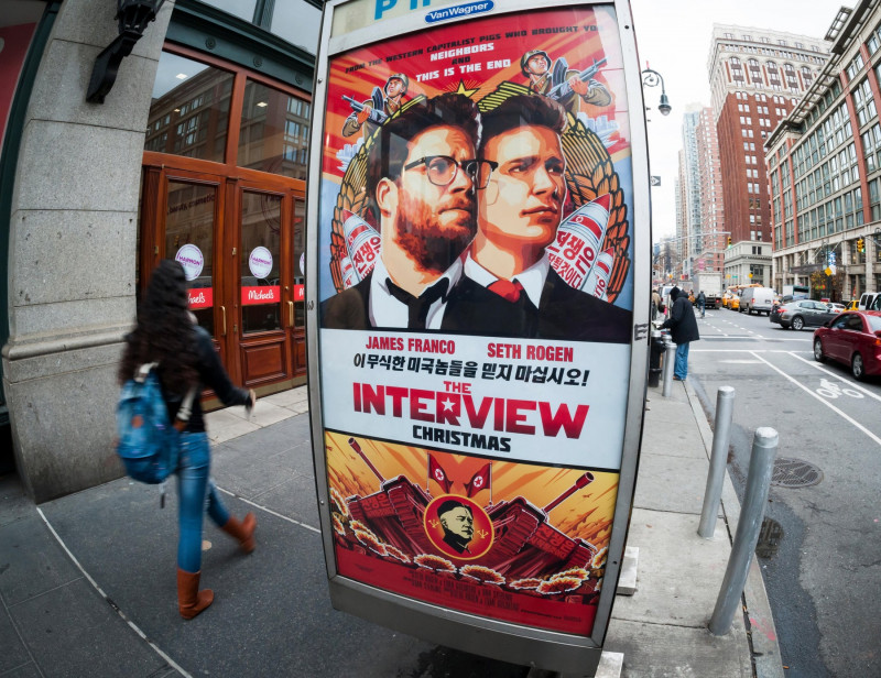 """New York, New York, USA. 17th Dec, 2014. Pedestrians walk past an advertisement for """"The Interview"""", a comedic film about North Korean leader Kim Jong-un's assassination, in New York on Wednesday, December 17, 2014. The planned premiere at the Landmark Su"""