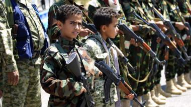 2 copii in costum de camuflaj, cu arme in mana, si tatii lor, inarmati si ei, in yemen