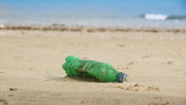 stica de plastic aruncata pe plaj.