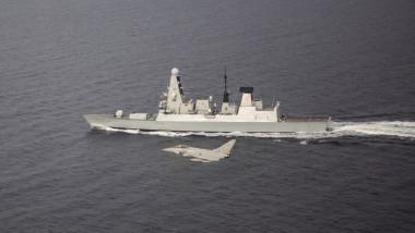 Distrugătorul HMS Defender al Royal Navy și un avion Eurofighter al RAF, în cadrul unor exerciții navale de anul trecut.