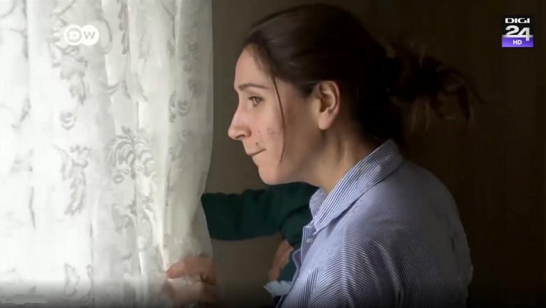 femeie cu copil in brate care se uita pe fereastra de dupa o perdea