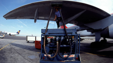 Mechanic refueling a commercial aircraft outside of an international departure gate at San Francisco International Airport.