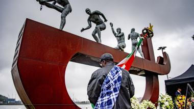 bărbat cu un steag în fața unui monument