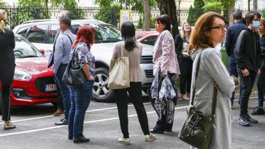 parinti care asteapta in fata scolii iesirea copiilor de la examen