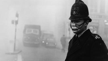 polițist britanic poartă o mască în anii 50 pentru a se proteja de smog.