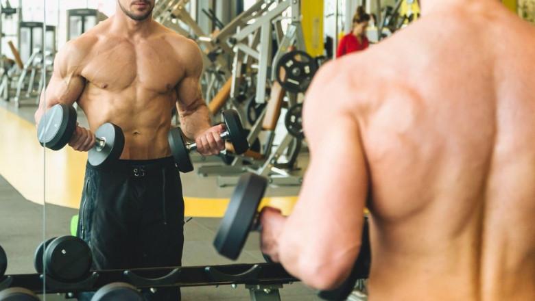 Un tânăr face exerciții de forță la sala de sport.
