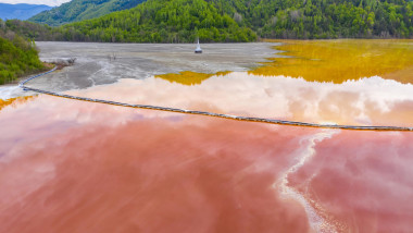 Aerial view of mining settling basin and lime supply. Colorful red polluted mine water from copper open pit excavation in Geamana, Rosia Montana, Roma