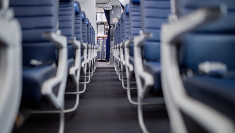 Empty dark blue passenger airplane seats in the cabin with narrow aisle in the middle. Peaceful and tranquil blue seats in a row in commercial plane.