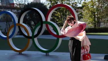 femeie cu masca in fata cercurilor olimpice