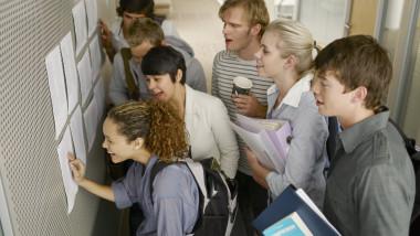 elevi se uita pe lista cu rezultatele la examen
