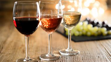 pahare cu trei soiuri de vin de culori diferite avand in spate ciorchini de struguri