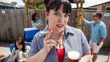 femeie care fumeaza si bea bere la un gratar