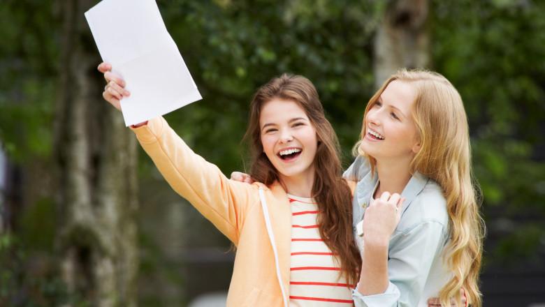 doua tinere se bucura de rezultatele la scoala