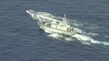 o barcă albastră din lemn cu un motor mic și cel puțin 20 de oameni la bord este urmărită în cercuri, cu viteză mare, de către Paza de coastă libiană.