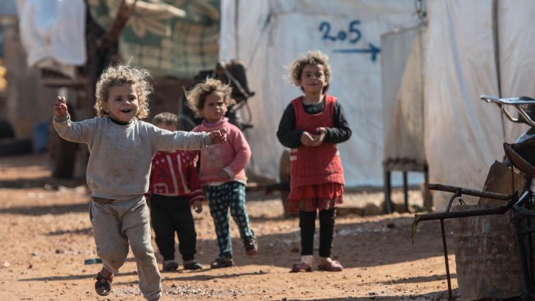 copii aleargă și se joacă într-o tabără de refugiați