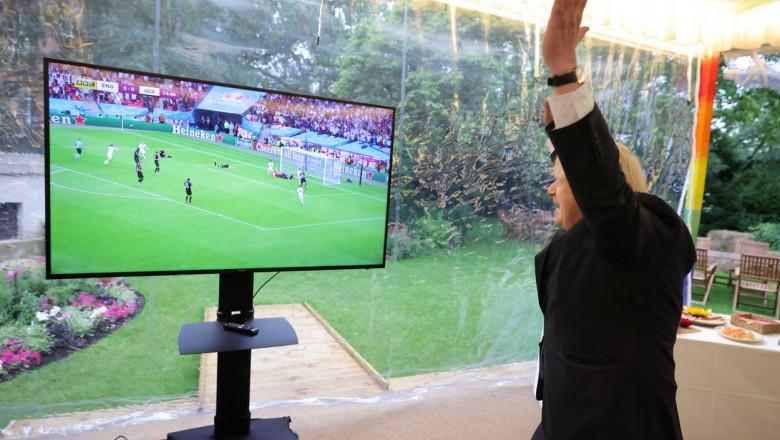 Boris Johnson cu mâinile în aer, uitându-se la meci la tv