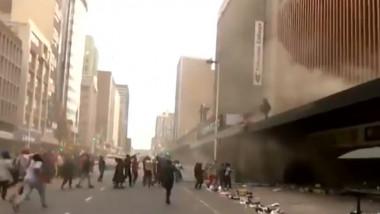un grup de oameni asteapta o femeie sa arunce un copil de pe o cladire din africa de sud