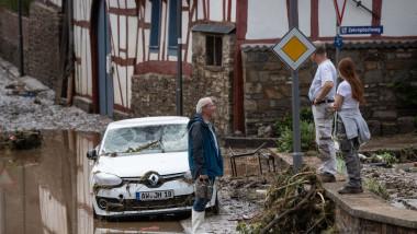 3 oameni stau de vorba langa o masina distrusa de inundatii in germania, apa pe strazi