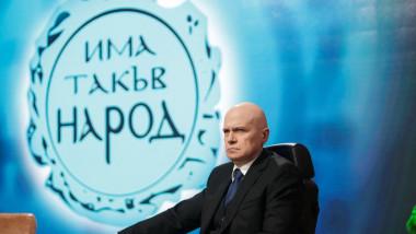 Bărbat chel, în costum, la un birou cu un ecran pe care este afișat un text în litere chirilice în spate