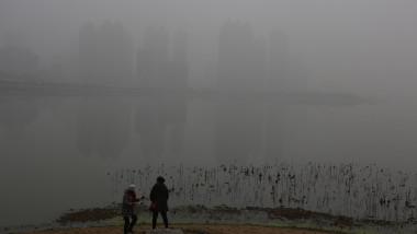 Doi oameni se plimă în orașul Wuhan îngropat de smog