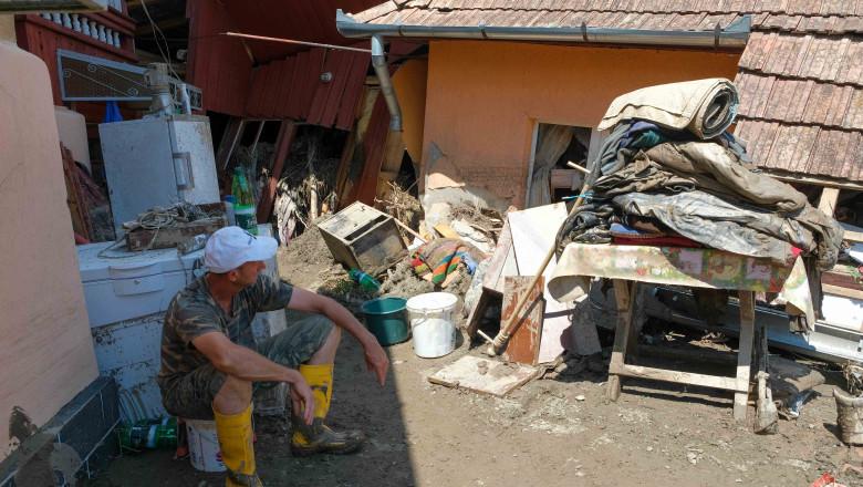 barbat care se uita la lucrurile scoase din casa in curte in urma unei inundatii