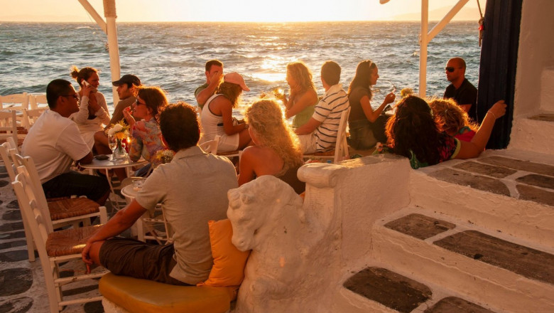 A group of people sitting in a bar in the village on the island of Mykonos in Greece on the waterfront at sunset. In the background the bright sky and