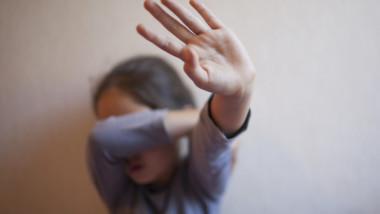 fetita care se fereste cu mainile