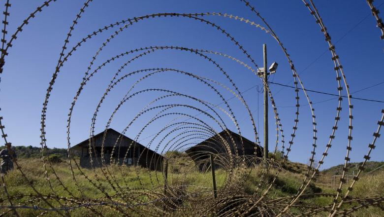 Cuba, Guantanamo Bay, two buildings seen through a razor wire.