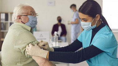 Woman doctor nurse in medical uniform and protective mask making vaccination senior elderly man