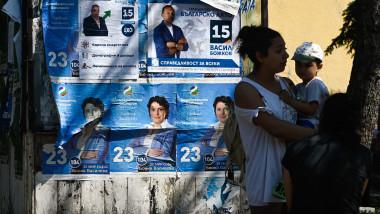 O femeie cu copilul ei așteaptă pe o stație de autobuz lângă afișele campaniei din Sofia pe 8 iulie 2021, înainte de alegerile parlamentare.