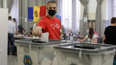un alegator cu masca baga in urna un buletin de vot