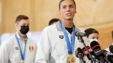 David Popovici, cu medalii la gât la sosirea pe aeroportul Otopeni.