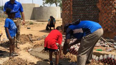 copil si adult in timp ce construiesc Casa din sticle