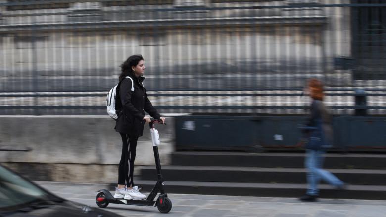 femeie care merge pe o trotineta electrica
