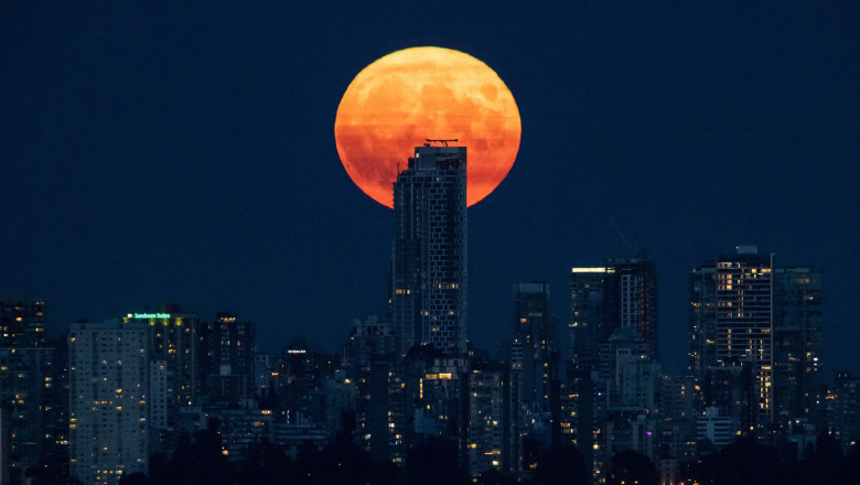A full moon rises behind One Burrard Place, a condo and rental home tower under construction which will be the city's third tallest building, in Vancouver,