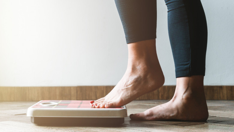 Female checking kilogrammes getting on the scale - self care and body positivity concept - warm flare on left